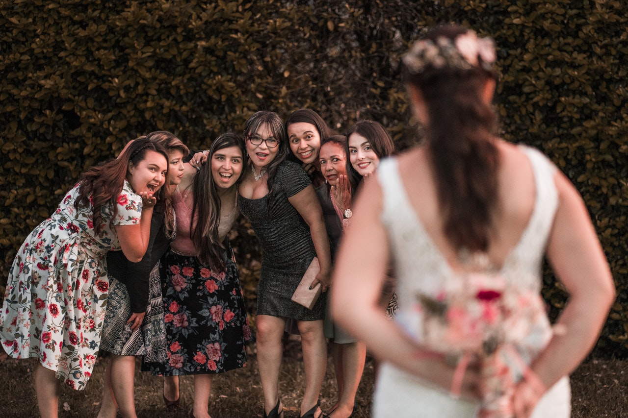 Cheerful multiethnic bridesmaids waiting for flower bouquet from unrecognizable bride