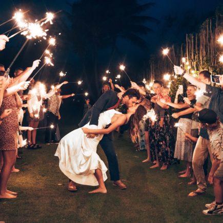 Loving Newlywed Couple Kissing among Wedding Guests