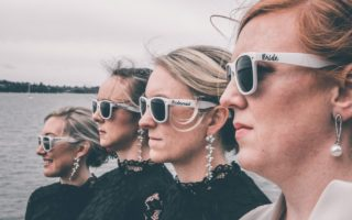 Stylish bride and bridesmaids in sunglasses standing on sea embankment on wedding day